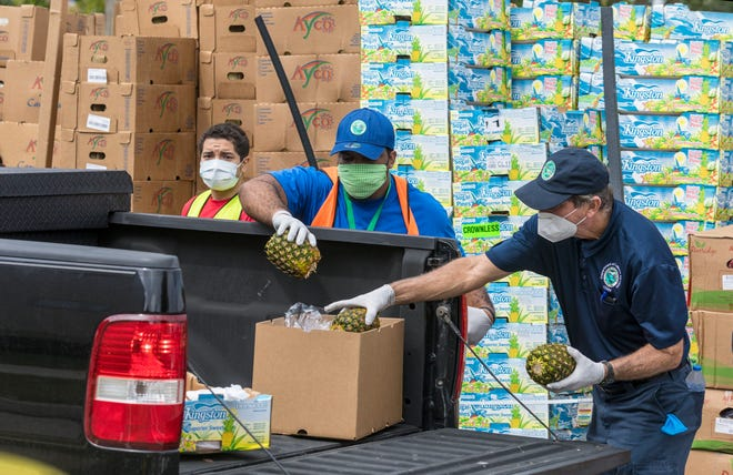 A mix of Greenacres city employees and volunteers load food from Feeding South Florida into vehicles at the Greenacres Community Center in April.  [LANNIS WATERS/palmbeachpost.com]