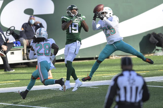 Miami Dolphins' Xavien Howard, right, breaks up a pass intended for New York Jets' Breshad Perriman, center, during the first half of an NFL football game, Sunday, Nov. 29, 2020, in East Rutherford, N.J. (AP Photo/Bill Kostroun)