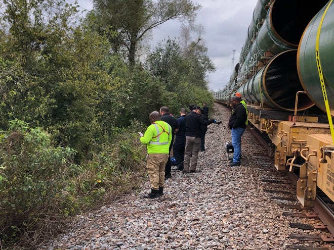 A crew from the Iberville Parish Sheriff's Office works the scene of a pedestrian fatality on a train track near White Castle on Monday.