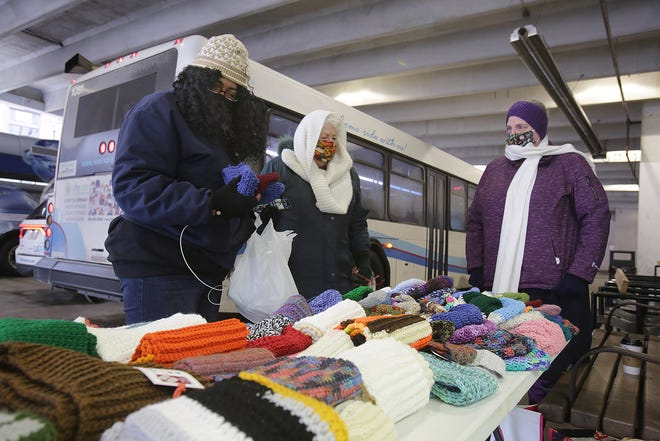 Lynn Dragomir (middle) and Jean Braden (right) with Stitches for Stark County, help Michele Thompson (far left) of Canton, pick out a scarf and hat at the Massillon SARTA station. The group of crafters teamed up with Warm Up America! to distribute the handmade items.