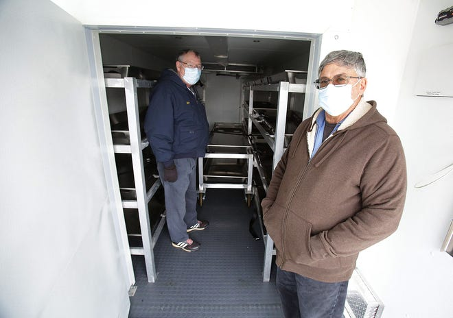 Investigator Rick Walters (left) and Stark County Coroner Dr. Anthony Bertin have a new morgue trailer on loan from the state.