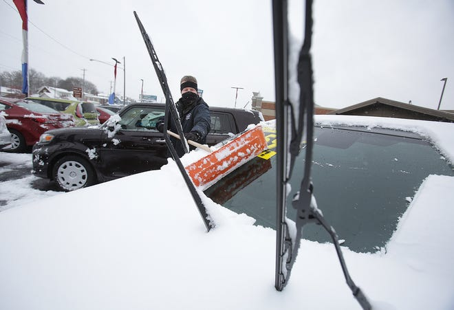 Kelly Crossen II clears snow Tuesday from the vehicles at his Perry Township lot Kelly's Auto Sales.