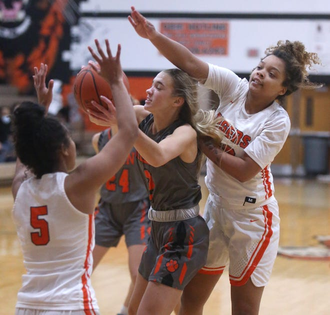 Olivia Payne, center, of Green fights for a rebound with Na Omie Moore and Kyra Watkins, right, of Massillon during their game on Monday. .