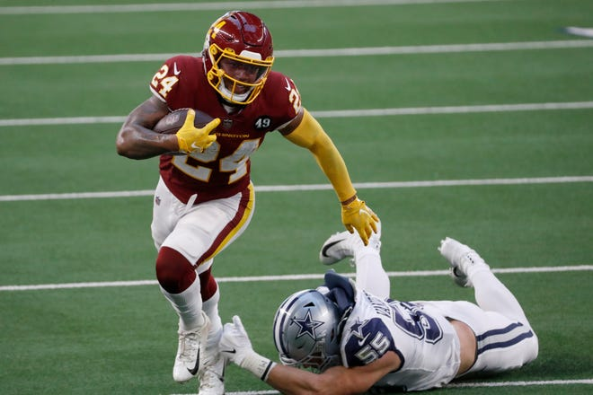 Washington Football Team running back Antonio Gibson (24) escapes a tackle attempt by Dallas Cowboys linebacker Leighton Vander Esch (55) in the first half in Arlington on Thanksgiving Day.