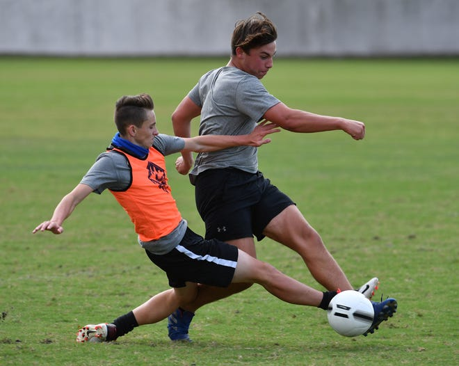 Defender Tyson Robere, left, slide tackles forward Tim Sheredy during the Lakewood Ranch boys soccer team practice on Monday. Max Preps has ranked the Mustangs first in the state and second in the country.