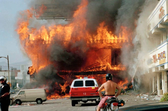 """A  shopping mall burns in Los Angeles on April 30, 1992, on the second day of rioting in the city following the Rodney King assault. The FSU/Asolo Conservatory play """"Twilight: Los Angeles, 1992"""" is about the beating and rioting."""