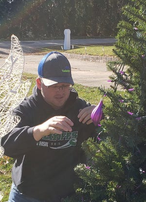 William Ornelas decorates a tree with purple ornaments in honor of his mother, who passed away just a few years ago.  The large outdoor displa is located at the corner of East  Prospect Street and Maple Avenue.