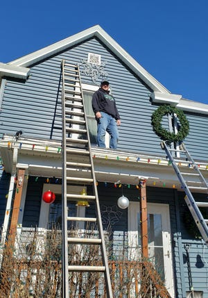 Willian Ornelas puts on the final touches of his traditional outdoor display from the roof. What started five years ago with a few strands of lights and Christmas trees has grown to almost 50 displays. The outdoor display is located on the corner of East Prospect Street and Maple Avenue and will be lit through the end of December.