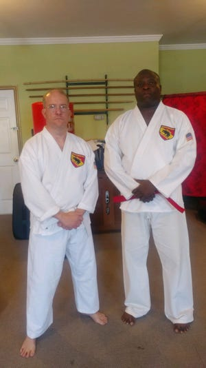 The New Bern School Of Martial Arts salutes James Florence a retired Navy Veteran who has served and protected this country for 20 years and has now completed basic training in Okinawan Shorin Ryu Karate and being promoted to advanced. He continues to encourage other veterans to stay active and involved with the community. James Florence (left) stands with his Karate Instructor Ronnie Lovick (right). [CONTRIBUTED PHOTO]