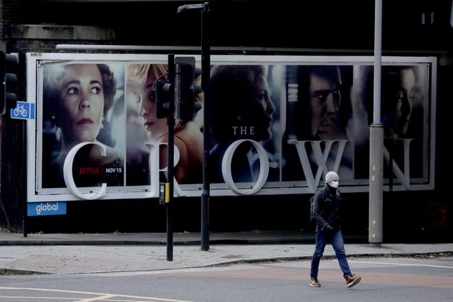 A man wearing a face mask walks past a billboard advertising 'The Crown' television series about Britain's Queen Elizabeth II and the royal family, during England's second coronavirus lockdown, in London.