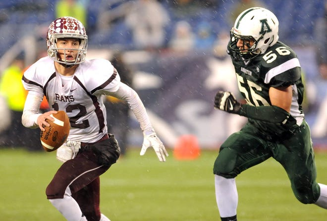Northbridge quarterback Koby Schofer is chased out of the pocket by Abington's Luca Cerasani in the Division 5 State Championship in 2014.