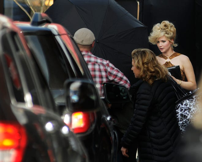 """Jennifer Lawrence exits Nick's Bar & Restaurant on Millbury Street in Worcester during the filming of """"American Hustle"""" in 2013."""