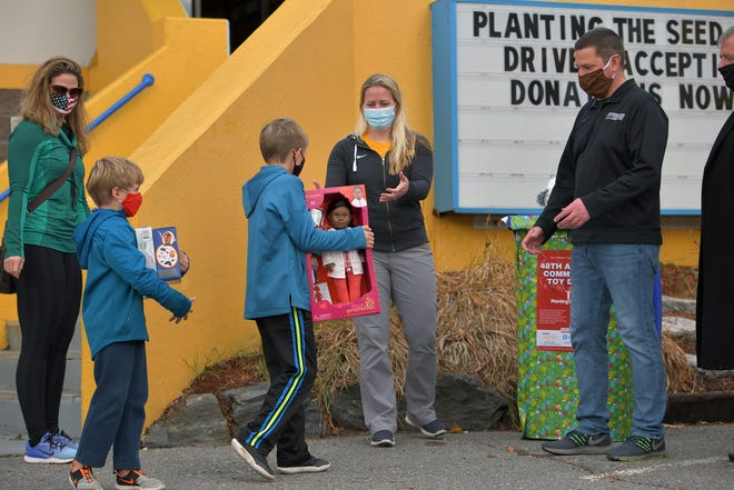Jennifer Thomas, left, stands near her sons, Parker, 6, and Cameron, 9, of Worcester, outside Worcester Fitness on Tuesday, as they hand over toy donations to Andrea Shliapa and Tim MacDonald for the Planting the Seed Foundation's 2020 virtual toy drive.
