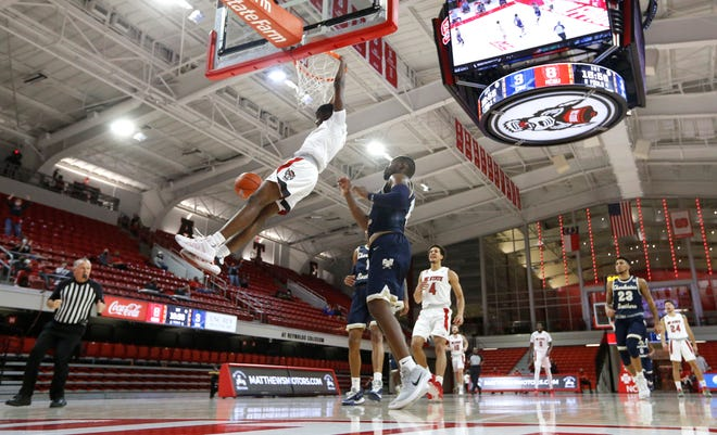 """N.C. State's Cam Hayes (3) said the Wolfpack's season opener on Nov. 25 against Charleston Southern felt like an """"old AAU game"""" because of the limited fans at Reynolds Coliseum. (Ethan Hyman/The News & Observer via AP)"""