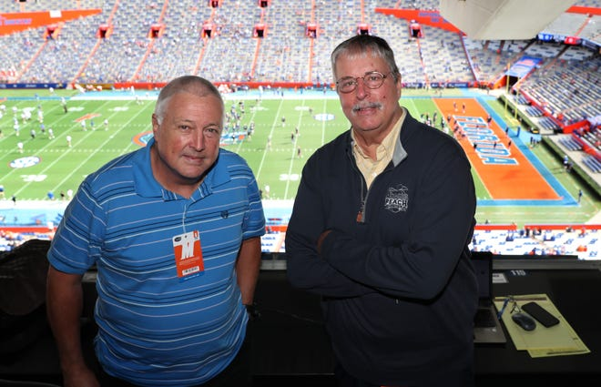 Robbie Andreu, left, and Pat Dooley, who retired Tuesday after a combined more than 60 years of sports reporting at The Gainesville Sun, pose for a photo in the press box at Ben Hill Griffin last Saturday.