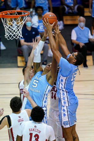 North Carolina forwards Armando Bacot and Garrison Brooks, right, go up in a crowd for a rebound during Monday night's opener against UNLV in the relocated Maui Invitational.