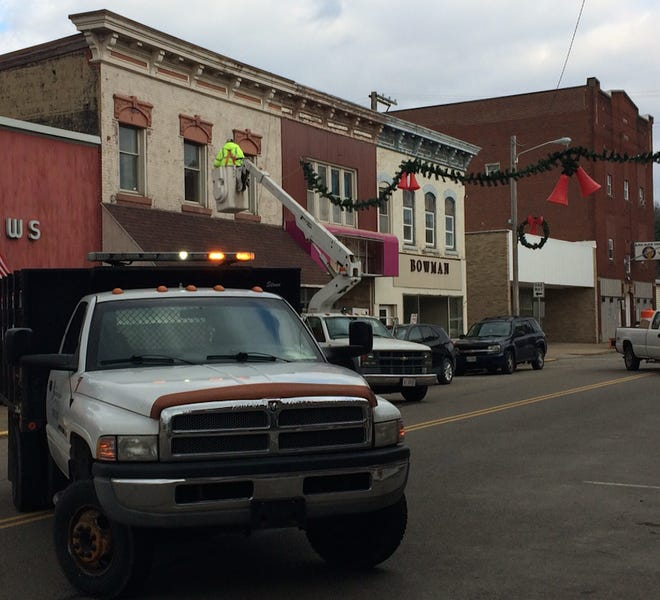 """In a picture supplied by """"Our Village - Newcomerstown,"""" volunteers work to put up the Christmas Bells on Main Street."""