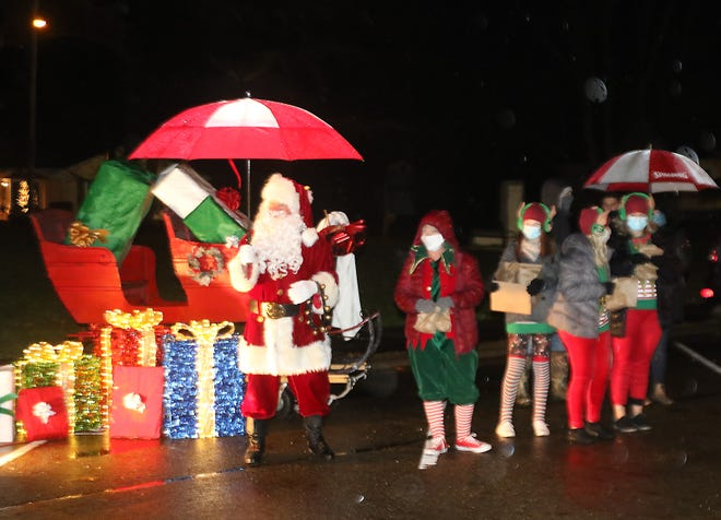 Santa Claus and his elves hand out goodies at the Twin City Stationary Christmas Parade Monday.  Exhibits were set up on 12th Street in Uhrichsville and remained in place for cars to drive past.