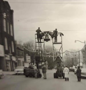 A crew supplied by the Village of Newcomerstown helped put up the Main Street Christmas decorations, including a recreation of Christmas bells that used to hang across Main Street over 40 years ago.