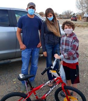 Jackson, 11, is all smiles behind his mask as he receives a new bike from Kyle and April Young.