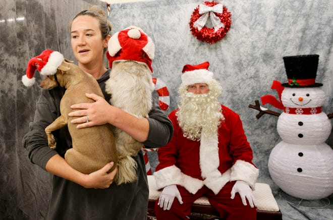 Kelli Garrick holds her dogs Roan and Vinni after they had photos taken with Santa Thursday, Dec. 5, 2019  in Tuscaloosa. [Staff Photo/Gary Cosby Jr.]