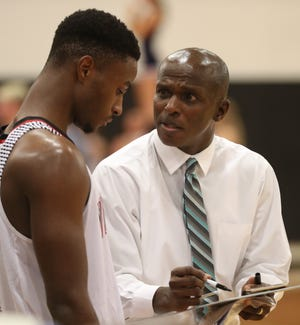 Whitehall-Yearling boys basketball coach Drew Williams reviews a play with Kei'Von Wiggins during a game last season. Wiggins, a senior forward, is one of the top returnees for the Rams, who are looking to improve on last year's 15-9 finish.