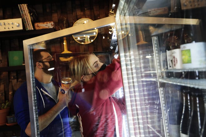 Employees Rachael Bitzer (center) and John Sweeney stock a refrigerator with beer while working at the Jackie O's On Fourth beer store at 171 N. Fourth St. in Columbus. The store, which belongs to Athens-based Jackie O's Pub & Brewery, opened for curbside pickup Nov. 24.