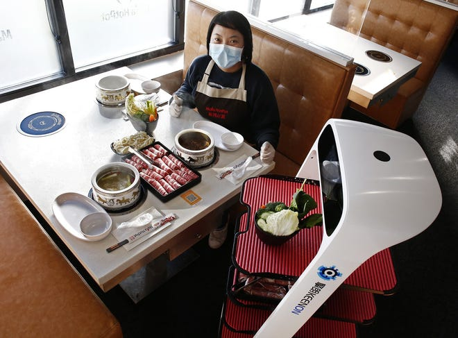Robot servers deliver food to diners at the new Mala HotPot restaurant, 3777 Park Mill Run Drive in Hilliard. Yvonne Cao, pictured Nov. 23, is manager of the restaurant.