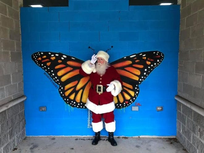 Sanata Claus poses in front of butterfly mural.