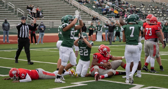 Waxahachie's Rolando Sierra (56) and Jace Robinson (22) signal for a safety after Waco quarterback Sean Mooney (19) was sacked in the end zone during Friday afternoon's game at Lumpkins Stadium. The Indians beat the Lions, 19-15.