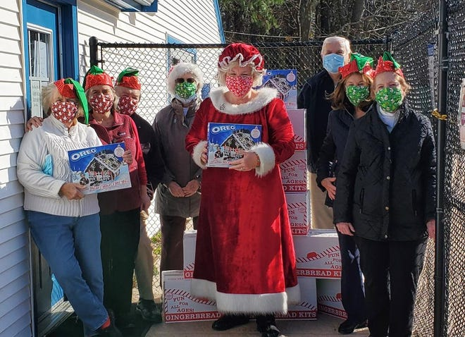 "Members of the Rotary Club of Scituate, along with ""Mrs. Claus,"" delivered gingerbread house kits to the students at the Cardinal Cushing Center."