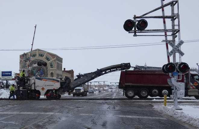 Despite the snow, a crew from Park Enterprise Construction Co. works Tuesday on the Norfolk Southern Railway line on North Sandusky Avenue just north of Washington Square.