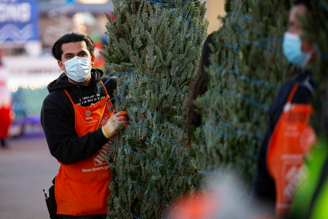 A Home Depot employee holds a Christmas tree during the Trees For All event at Home Depot on South Port Avenue on Monday, Nov. 30, 2020. The event, now in it's 23rd year, awards trees to families for the holidays.