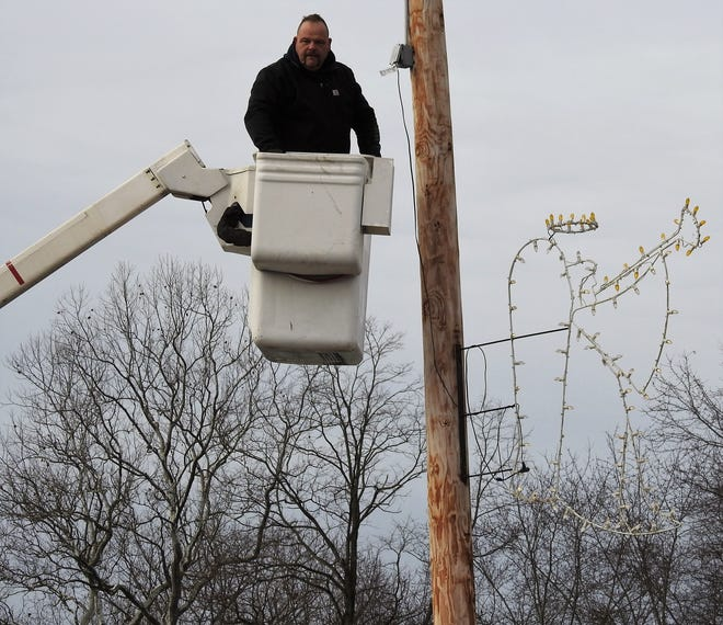 Dave Stone finishes hanging a Christmas decoration on a pole in Warsaw in a bucket truck by the Walhonding Valley Fire Departement.