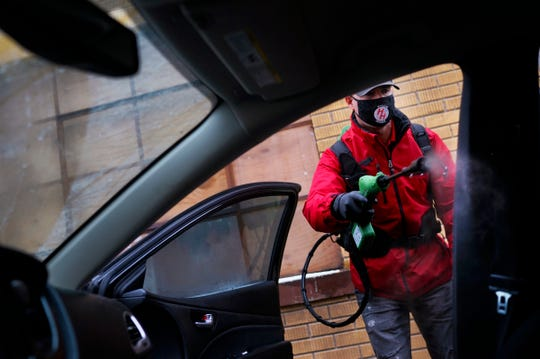"""Joe Kulberg, Director of Operations at Enviro-Master Services, demonstrates their drive-thru sanitizing service on Tuesday, Dec. 1, 2020, in Warren. The service utilizes an EPA approved disinfectant with their """"Virus Vaporizer"""" tool to sanitize cars. The service is available Monday through Friday, 10 a.m. to 2 p.m."""