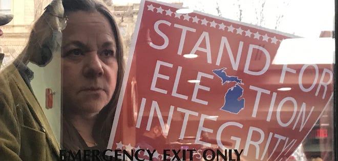 Seorang demonstran memegang tanda sambil melihat melalui pintu keluar darurat kaca di luar rapat Komite Pengawas Senat Michigan pada Selasa, 1 Desember 2020.