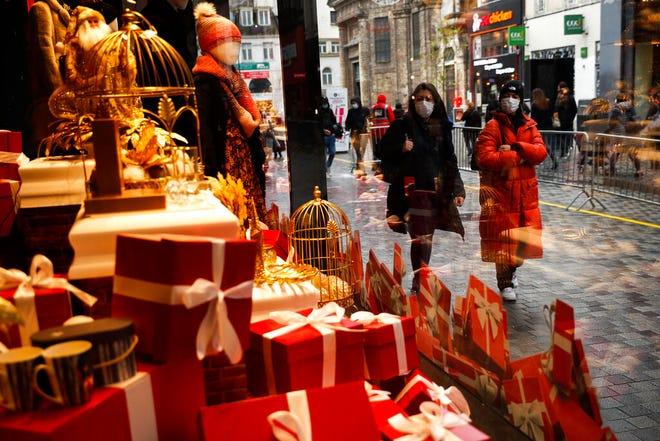 Orang-orang, yang mengenakan masker untuk mencegah penyebaran virus corona, berjalan melewati jendela etalase sebuah pusat perbelanjaan di jalan komersial di pusat kota Brussel, Selasa, 1 Desember 2020.