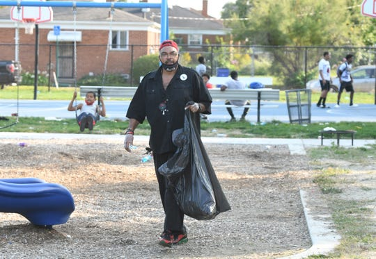 Malik Shabazz picks up debris at Dequindre Grixdale Park in Detroit during an event in which his community group registered voters and passed out Crime Stoppers flyers.