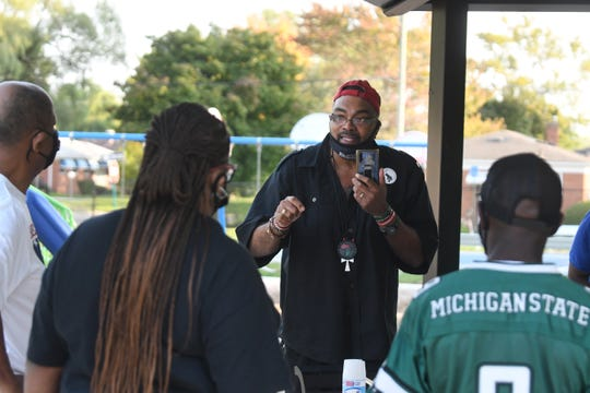 Malik Shabazz speaks to community members at Dequindre Grixdale Park in Detroit, while also handing out Crime Stoppers flyers seeking information on the hit-and-run death of Steven Radcliff. Shabazz said he'd like to see more people come out to events like the one at Dequindre-Grixdale Park.