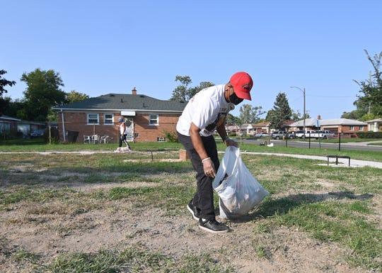 Deacon Robert Bruce picks up debris at Dequindre Grixdale Park  in Detroit.