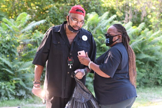 Beverly Winfrey, mother of hit-and-run victim Steven Radcliff, speaks with Malik Shabazz as they passed out Crime Stoppers flyers while cleaning up Dequindre Grixdale Park in Detroit.