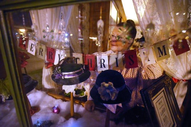Dolly Scheibelhut mengintip ke luar jendela Mrs. Cohen Millinery saat tamu keluar masuk toko pada Selasa malam di Greenfield Village.'Malam Liburan' di Greenfield Village di Dearborn, Michigan pada 19 Desember 2017.