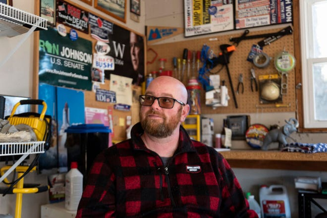 Fond du Lac County Republican Party Chairman Rohn Bishop is seen in the workshop at his home in Waupun, surrounded by posters of fellow Republicans.