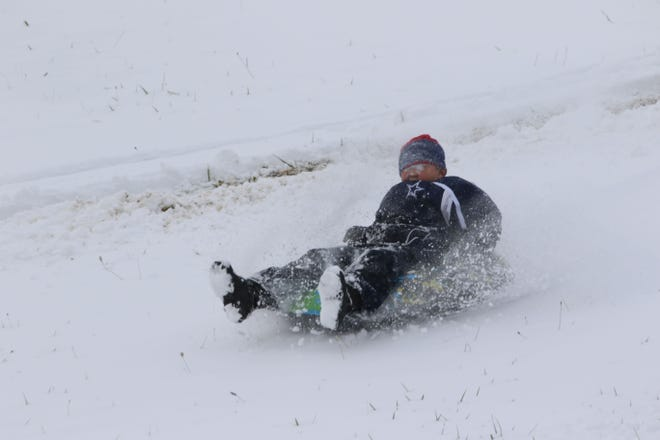 Alikye Parks, 9 years old of Fremont, enjoys a day of sledding at the Fremont Reservoir on Tuesday as Sandusky County recorded the first measurable snowfall of the season.