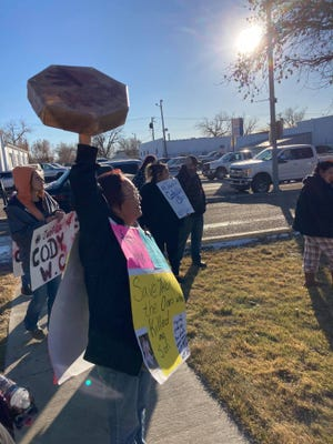 Frances Weeks-Combs raises a drum and wears signs, calling for justice for her son Cody Weeks Combs.