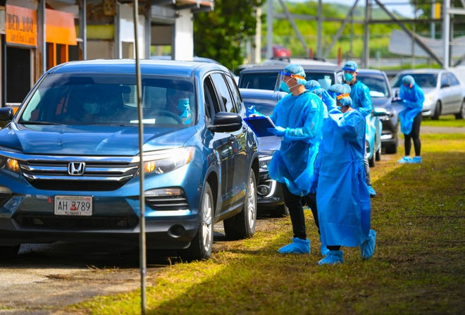 Department of Public Health and Social Services personnel offer COVID-19 tests during drive-through testing at the old carnival grounds in Tiyan in this Dec. 1 file photo.