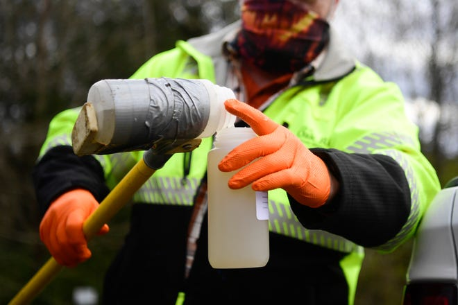 Mike Brown of the public works department for the City of Oak Ridge, pours a sample of waste water for coronavirus testing at Big Turtle Park in Oak Ridge, Tuesday, Dec. 1, 2020.