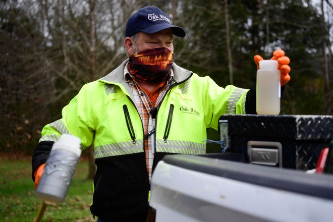 Mike Brown of the public works department for the City of Oak Ridge, collects waste water for coronavirus testing at Big Turtle Park in Oak Ridge, Tuesday, Dec. 1, 2020.