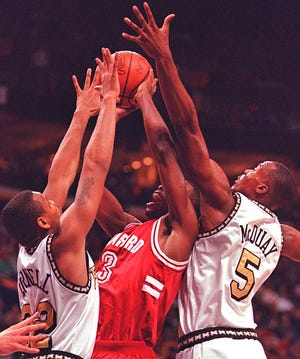 Purdue's Jaraan Cornell (left) and Gary McQuay sandwich Stanford's Kris Weems in the 1998 NCAA tournament.