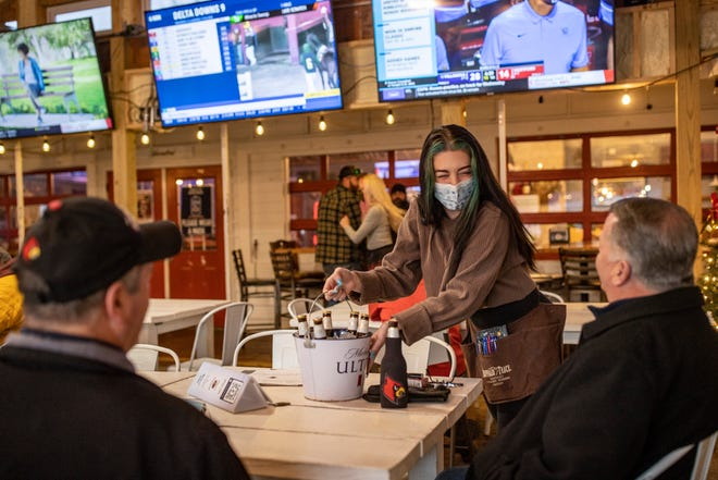 """Joe's """"Older than Dirt"""" waitress, Josie Olliges, waits on patrons in the outdoor seating space Tuesday evening. Dec. 1, 2020"""